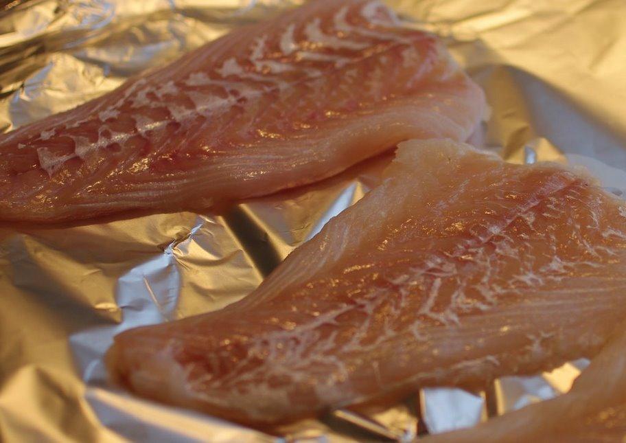 Rå torskefilet klar til krydring, rulning, indpakning i bacon og grillning under ovn